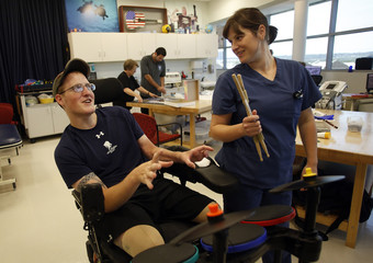 Sgt. Matt Krumwiede, of the U.S. Army, reacts to occupational therapist Kelley Wells after playing drumming video game during occupational therapy at the Center for the Intrepid at Brooke Army Medical Center in San Antonio, Texas