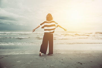 Women freedom single travel concept. Girl free emotion body language at the sea beach with sun light vintage color tone.