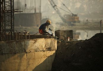 Labourer wields at the construction site of a bridge being built over the river Yamuna for metro rail in New Delhi