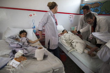 Nurse Burwood holds the hand of Gullali, who sustained bullets injuries, during a follow-up visit of patients at Emergency hospital in Kabul
