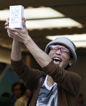 A man holds up his new Apple iPhone 5S box after he waited for it since September 10, outside an Apple Store at Tokyo's Ginza shopping district