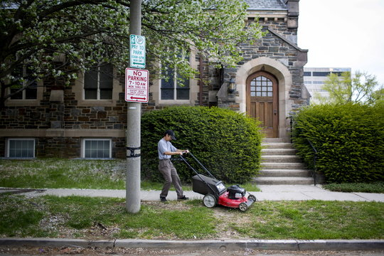 A man mows a lawn in Towson, Maryland