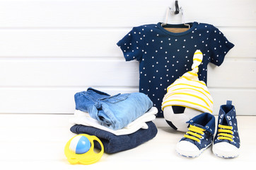 Baby boy clothing set (blue t-shirt with white stars, jeans shirt, sneakers with yellow shoelaces, striped hat) and toys. Wish list or shopping overview for pregnancy and baby shower. View from above.