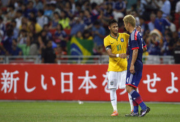 Brazil's Neymar talks with Japan's Keisuke Honda after their friendly soccer match at the national stadium in Singapore