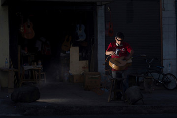 Ecuadorian luthier Ivan Ibujes paints a guitar after repairing it at his shop in Quito