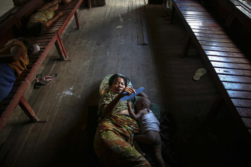 A woman breastfeeds her baby as people sleep inside a circular train stopped at Yangon's central station