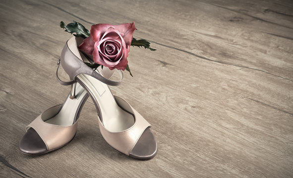 Argentine tango shoes and a rose on a wooden floor, space