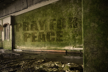 text pray for peace on the dirty wall in an abandoned ruined house