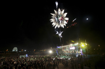 Fireworks explode as supporters of the political party All Pakistan Muslim League (APML) take part in a rally addressed by their party president Pervez Musharraf via video link (unseen) from Dubai, near the mausoleum of Mohammad Ali Jinnah in Karachi