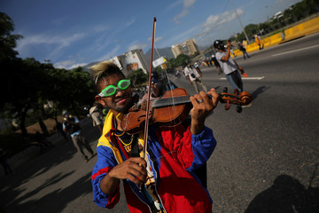 An opposition supporter plays the violin during a rally against President Nicolas Maduro in Caracas