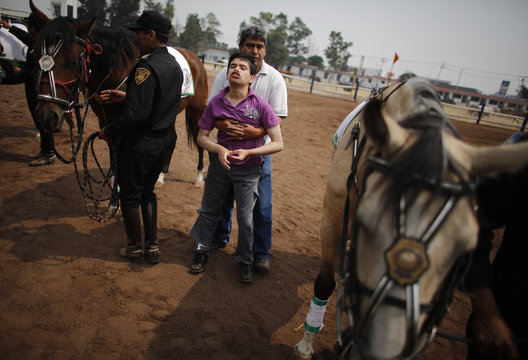 Man holds his handicapped son after a session of equine-assisted therapy at the Mounted Police Unit in Mexico City