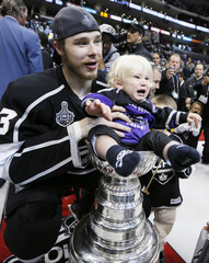 Kings' Dustin Brown holds his son in the Stanley Cup after his team defeated the Devils during Game 6 of the NHL Stanley Cup hockey final in Los Angeles