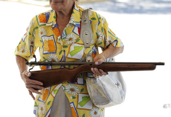 "A 72-year old woman holds a 22 mm calibre rifle before turning it in during the ""Voluntary Disarmament Programme"" in San Nicolas in Monterrey"