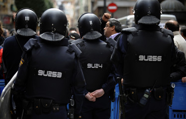 Spanish riot police officers stand guard during a demonstration in Oviedo