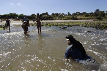 """Tourists take pictures as the head of the NGO """"S.O.S Rescate Fauna Marina"""" Tesore takes bath a male baby seal in sea near seaside resort of Piriapolis"""