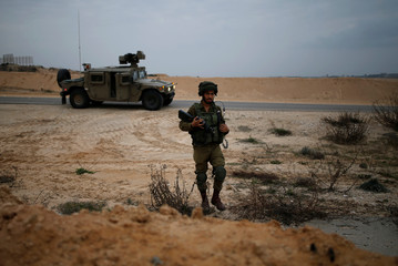 An Israeli soldier patrols the Israeli side of the Israel-Gaza border