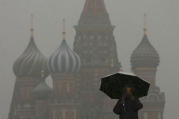 A man walks under an umbrella during a snowfall, with St. Basil's Cathedral seen in the background, in Red Square in central Moscow
