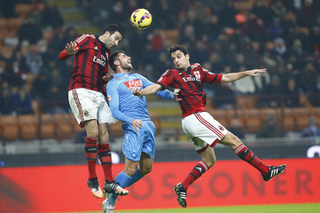 AC Milan's Bonaventura and Rami jump for the ball with Napoli's Lopez during their Italian Serie A soccer match at the San Siro stadium in Milan