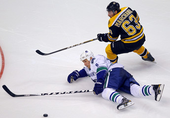 Vancouver Canucks defenseman Sami Salo battles for posses ion of the puck with Boston Bruins left wing Brad Marchand in second period action in Boston