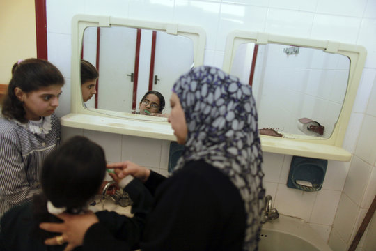 Teacher guides student as she brushes her teeth during lesson to visually impaired Palestinian students on daily life living at UNRWA-run al-Nour (Light) School for the Blind and Visually Impaired Children in Gaza City