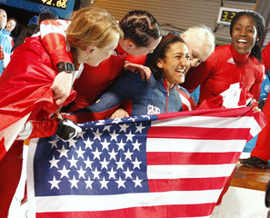 Bronze medalist Meyers celebrates with Canada gold and silver medalists after the women's bobsleigh at the Vancouver 2010 Winter Olympics