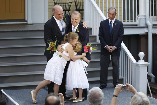 New York City Mayor Bloomberg stands back after presiding over the wedding of Mintz, the city's consumer affairs commissioner, and Feinblatt, a chief adviser to the mayor in New York