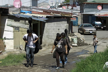Youths walk to attend their music lessons at the SIFAIS center in the poor neighborhood of La Carpio