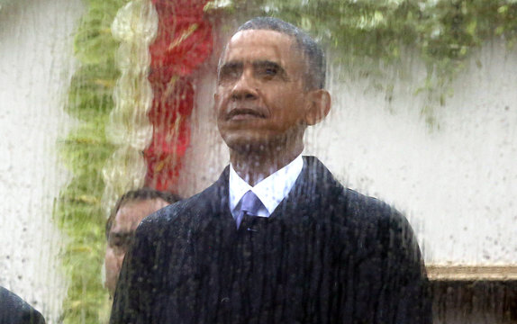 U.S. President Barack Obama looks up at the sky as he watches India's Republic Day parade from behind rain streaked bullet proof glass in New Delhi
