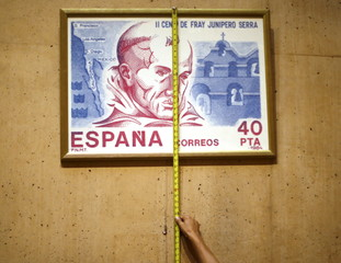 A worker hangs a stamp design of Friar Junipero Serra, who will be canonized next week by Pope Francis, in a new chapel to honor Serra at the Cathedral of Our Lady of the Angels in Los Angeles