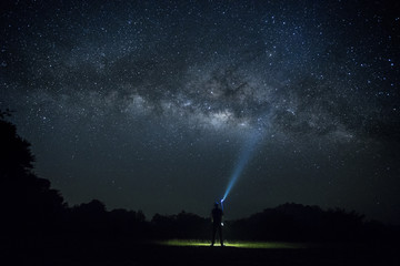 The Man point flashlight to the milky way galaxy, Night sky with stars, Long exposure photograph, with grain.