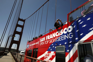 Tourists snap pictures of the Golden Gate Bridge from a bus in San Francisco