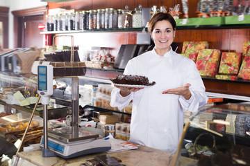 Female seller offering festive chocolate cake