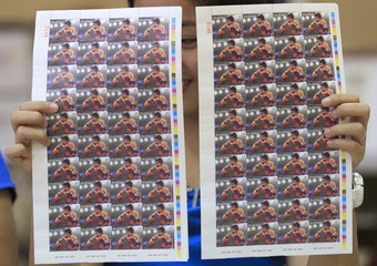 """Postal worker shows the limited copies of """"Fight of the Century"""" postage stamps of WBC boxer Manny Pacquiao to the photographers inside the main post office in Manila"""