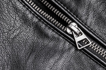 Shiny metal silver zipper. Black leather jacket fashion background.
