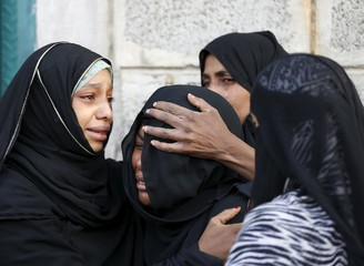 Women comfort another woman as she mourns for her father, who was killed by a Saudi-led air strike, in Yemen's capital Sanaa