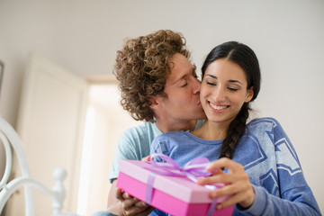 Woman receiving gift  in pink box from boyfriend in their bedroom
