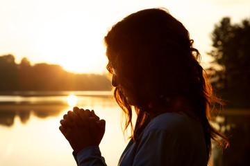 Woman in prayer at sunrise by lake