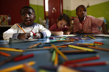 Children play with colouring pencils at Il Giardino di Madre Teresa, a nursery school where some students are the children of migrants, in  Palermo