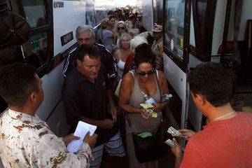 Stranded tourists pay for bus tickets to San Diego airport after being airlifted by the Mexican Army from Los Cabos, at the international airport of Tijuana