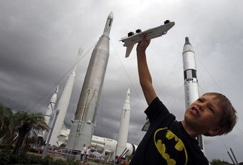 Freddy Porter of Raleigh N.C. plays with a toy space shuttle in the Rocket Garden of the Kennedy Space Center Visitor Complex near Cape Canaveral