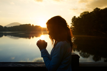 Woman in prayer by lake at sunrise Fotomurales