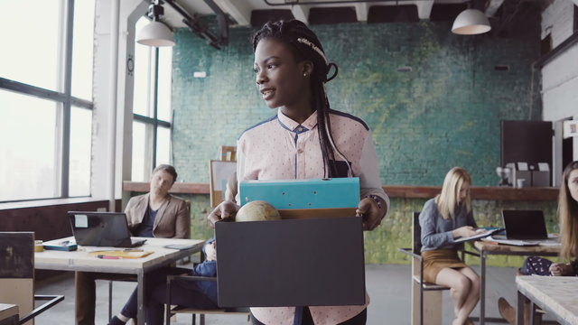 Young african woman getting fired from work. Female walks through the office, carrying box with personal belongings.
