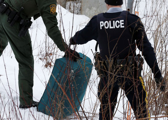 U.S. Customs and Border Protection officer and RCMP officer handle luggage of a woman who told police that she and her family were from Sudan, after being taken into custody upon walking across the U.S.-Canada border into Hemmingford, Quebec