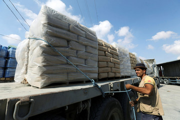 A Palestinian man stands next to a truck loaded with bags of cement at the Kerem Shalom crossing between Israel and southern Gaza Strip