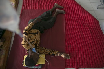 A migrant who arrived in Indonesia last week by boat receives medical treatment at a temporary shelter in Aceh Timur regency