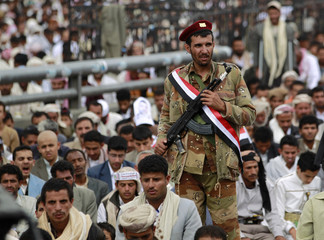 A defected army soldier stands guard as anti-government protesters perform weekly Friday prayers during a rally in Sanaa