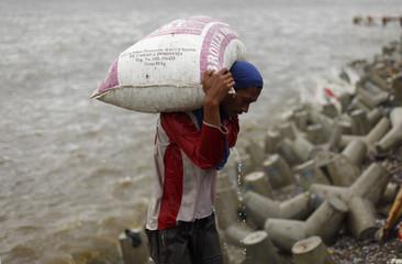 Supadi Bewok, a daily wage worker, carries a sack of mussels along the breakwater at Muara Baru beach in Jakarta