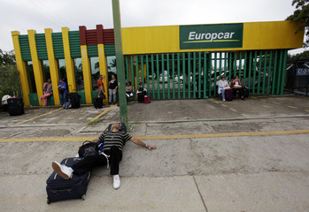 Stranded passengers are seen outside a rental car office as protesters block access to airport during a protest in reprisal for the killing of 43 trainee teachers, in Acapulco