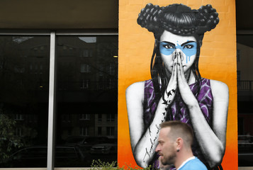 A man walks past a mural which is part of the Urban Nation art project in Berlin