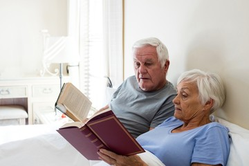 Senior couple reading books in the bedroom